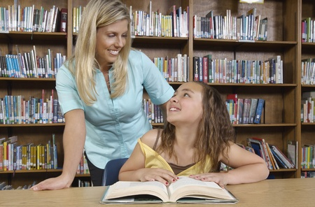 School girl reading book with teacher in library Stock Photo - 12592462
