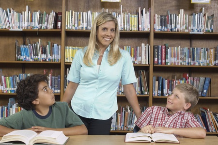 Two school boys with teacher in library Stock Photo - 12592464