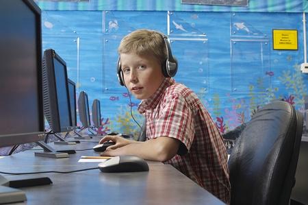 School boy wearing headphones in computer room Stock Photo - 12592467