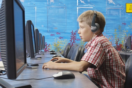 School boy wearing headphones in computer room Stock Photo - 12592469