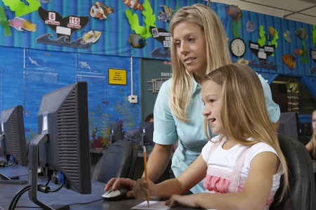School girl using computer with teacher in classroom Stock Photo - 12592478