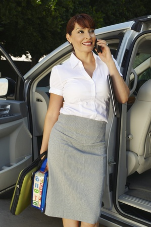 Business woman using mobile phone beside car Stock Photo - 12592492