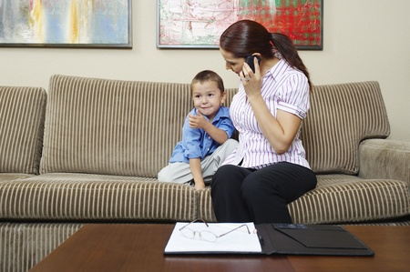versatile: Businesswoman Working at Home with Son