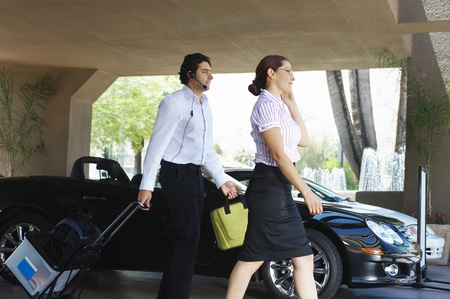 Business couple with luggage passing car Stock Photo - 12592499