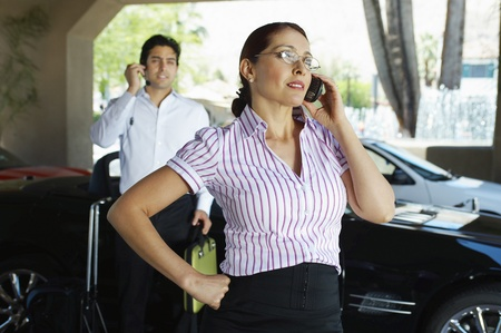 Business couple using mobile phones near car Stock Photo - 12592500