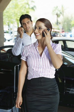 Business couple using mobile phones near car Stock Photo - 12592502