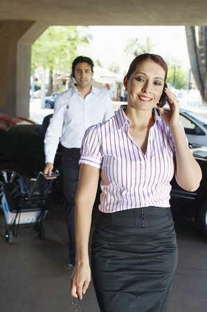 Business couple using mobile phones near car Stock Photo - 12592503