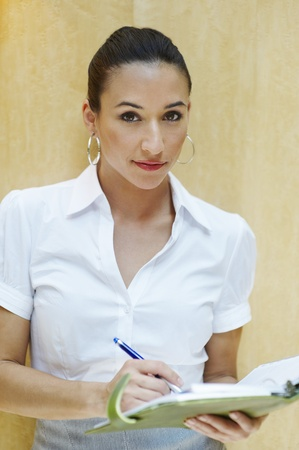 writing activity: Young business woman holding notepad