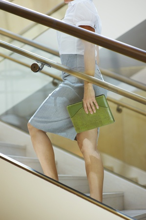unknown age: Business woman walking up stairs mid-section