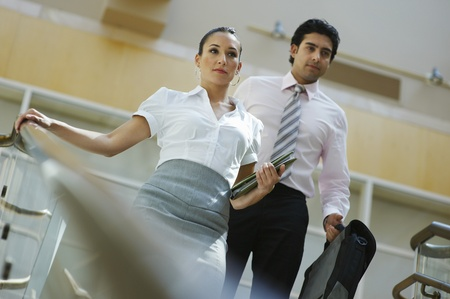 low blouse: Young business woman and business man walking down stairs LANG_EVOIMAGES