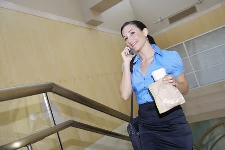 Business woman holding lunch using mobile phone Stock Photo - 12592549