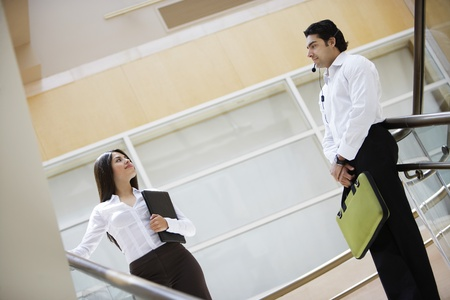 low blouse: Business woman and business man talking on stairs