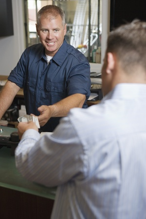 40 to 45 year olds: Man Paying for Repair Work LANG_EVOIMAGES