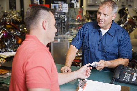 40 to 45 year olds: Customer in Motorcycle Shop Paying LANG_EVOIMAGES