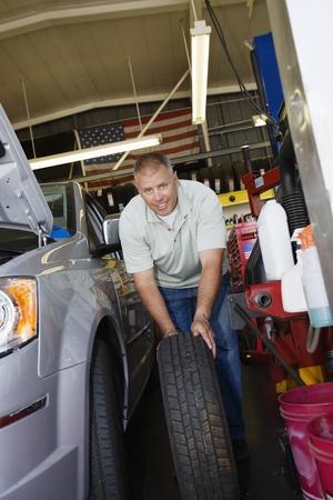 Auto Mechanic Changing a Tire Stock Photo - 12592638