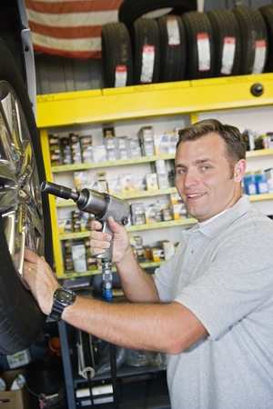 Mechanic Changing a Tire Stock Photo - 12592640