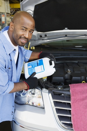 40 to 45 years old: Auto Mechanic Adding Fluids to Minivan