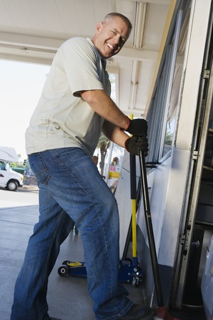 40 to 45 years old: Man Jacking up Vehicle in Service Station