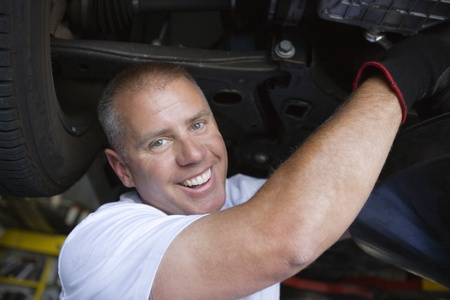 40 to 45 years old: Auto Mechanic Working on Car