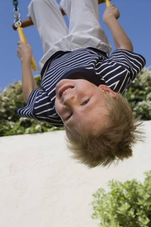 Little Boy Upside Down on a Swing Stock Photo - 12592689