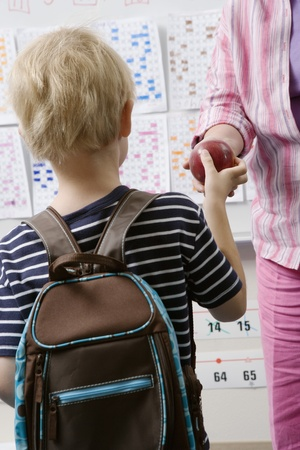 Little Boy Handing Teacher an Apple Stock Photo - 12592695