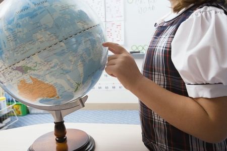 grade school age: Little Girl Pointing to Globe