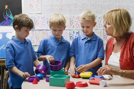 Teacher Helping Little Boys Assemble Educational Puzzle Toys Stock Photo - 12592713