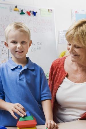 late fifties: Teacher Watching Little Boy Assemble Educational Puzzle LANG_EVOIMAGES