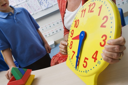 cropped out: Teacher Demonstrating Time to Children LANG_EVOIMAGES