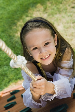 Dressed up Little Girl Climbing a Rope Stock Photo - 12592724