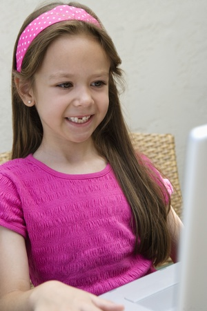 6 7 year old: Smiling Little Girl Using a Laptop LANG_EVOIMAGES