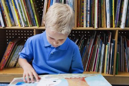 grade school age: Little Boy Reading a Picture Book