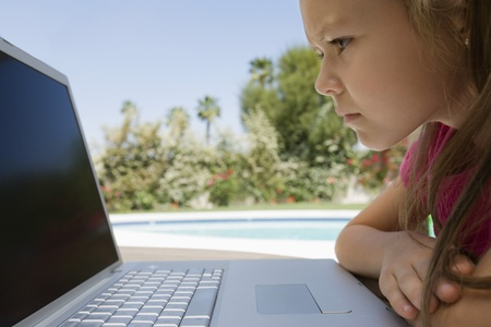 Serious Little Girl Using a Laptop Stock Photo - 12592770