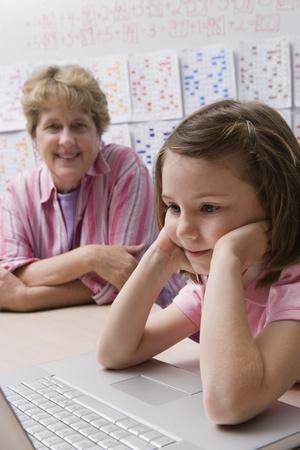 late fifties: Teacher Watching Schoolgirl Use Laptop