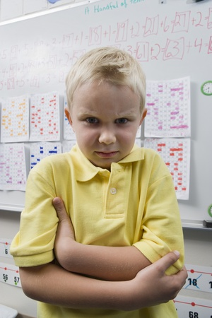 half length posed: Angry Little Boy in a Classroom LANG_EVOIMAGES