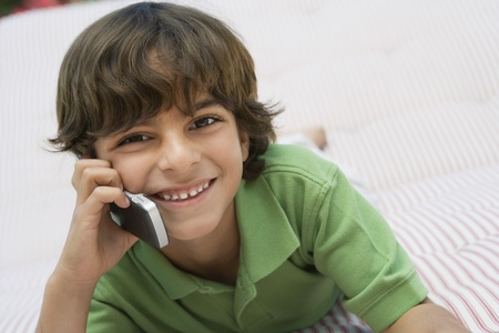 6 year old children: Young Boy Using Cell Phone LANG_EVOIMAGES