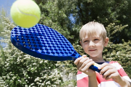 6 7 year old: Boy Playing with Paddle and Ball