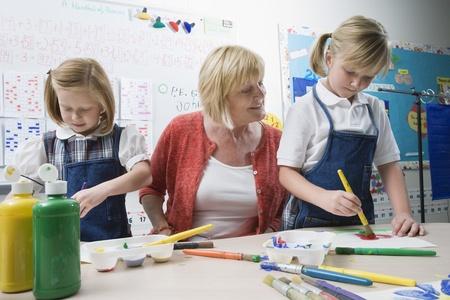 nursery education: Teacher Watching Students Paint