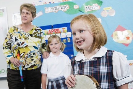 elementary student: Elementary Student with Tambourine in Music Class LANG_EVOIMAGES