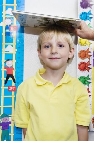 half length posed: Boy Getting Height Measured LANG_EVOIMAGES