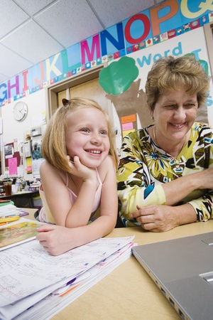 Teacher and Elementary Student Looking at Laptop Stock Photo - 12592901