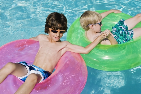 Boys on Float Tubes in Swimming Pool Stock Photo - 12592905