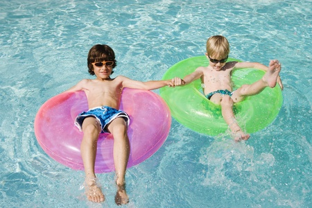 swimming to float: Boys on Float Tubes in Swimming Pool