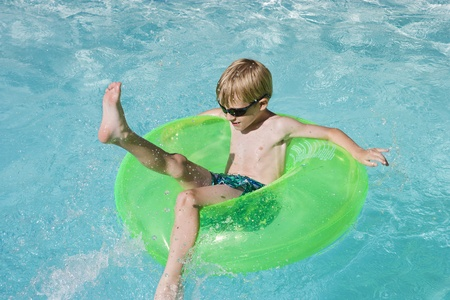 float: Boy on Float Tube in Swimming Pool