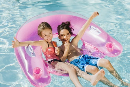 vacationer: Children Playing on Inflatable Toy in Swimming Pool
