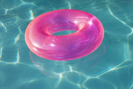 float tube: Pink Float Tube Floating in Swimming Pool LANG_EVOIMAGES