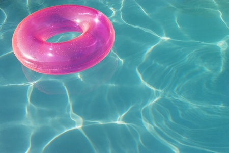Pink Float Tube Floating in Swimming Pool Stock Photo - 12592915