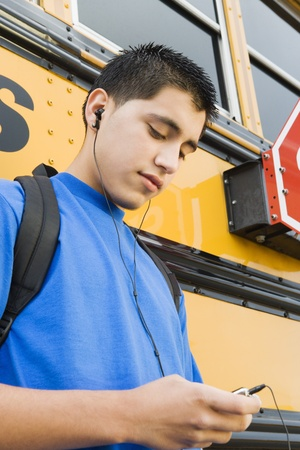 only one teenage boy: High School Boy With MP3 Player by School Bus