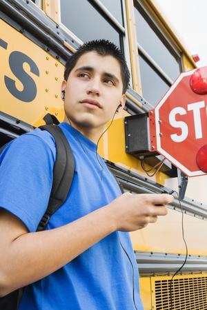 teenaged boys: High School Boy With MP3 Player by School Bus