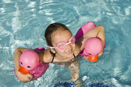 Girl Floating Using Two Pink Rubber Ducks Stock Photo - 12592936